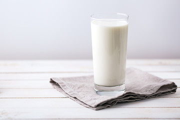 Glass of milk on white rustic wooden background