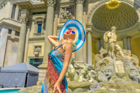 Happy woman with hat enjoying in front of roman empire style facade with columns and statues of popular shopping mall in Las Vegas Strip. Happy lifestyle tourist in Nevada, Unites States.