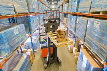 Distribution warehouse worker moving cardboard box on forklift truck