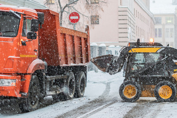 excavator load snow in truck. clearing streets of snow b