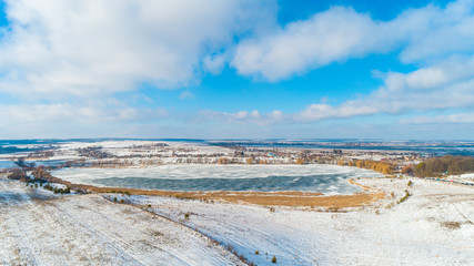 Aerial Drone Photograph of a Partly Frozen Lake Surrounded with Beautiful Winter Colors of the Fields and Forest