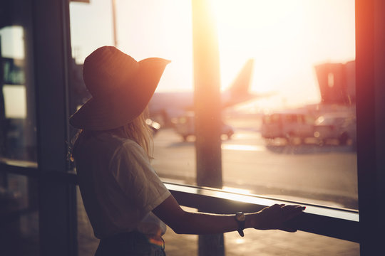 Young woman tourist in straw hat writes messages via smartphone at airport near terminal. Travel concept
