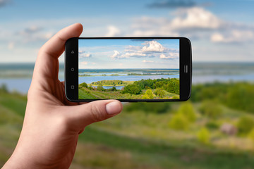 Smartphone in hand photographs nature on the screen. Photos of the scenery of the evening river.