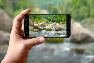 Smartphone in hand photographs nature on the screen. Photos of the mountain river for posting on social networks.