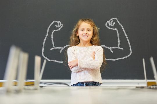 Mädchen in Schule steht vor Tafel mit Muskeln