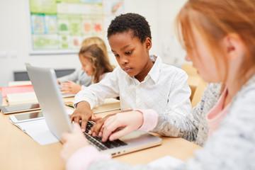 Afrikanischer Junge schreibt auf dem Laptop