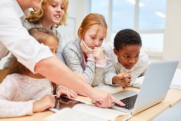 Lehrer hilft bei der Arbeit am Laptop Computer