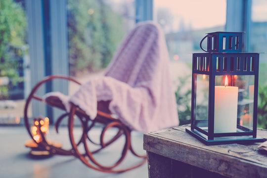 Lampion, bougie et chaise à bascule dans une ambiance cocoon à la maison.