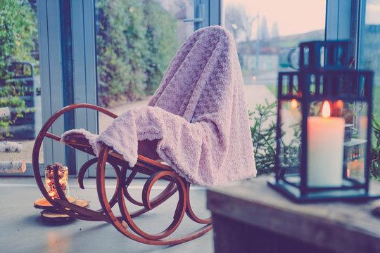 Chaise à bascule, lampion et bougie dans une ambiance cocooning à la maison.