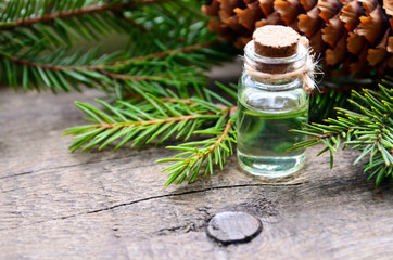 Fir essential oil in a glass bottle and green coniferous tree branches with cones on old wooden table.Spruce aroma oil for spa,aromatherapy and bodycare.Selective focus.