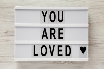 Modern board with text 'You are loved' on a white wooden surface, top view. Flat lay, overhead. Closeup.