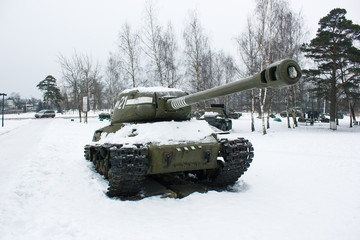 View of the military tank under the snow in the winter Park