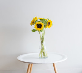 Sunflowers in glass vase on small white round table against neutral wall background