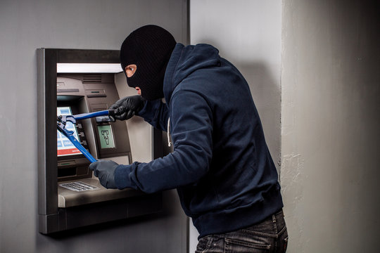 Thief with bolt cutter hacks an ATM. Law and crime concept