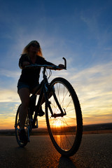 Woman riding a mountain bike at sunset. Sport and active life concept.