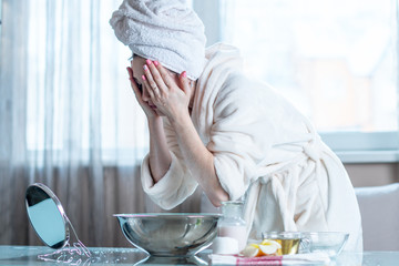 Young woman with a towel on her head washing face with water in the morning. Hygiene and care for the skin at home