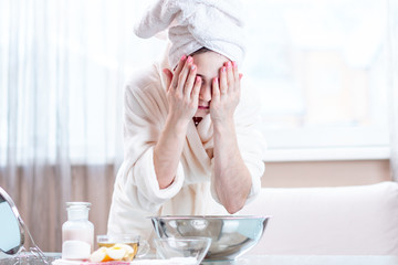 Young woman with a towel on her head washing her face with water in the morning. Hygiene and care for the skin