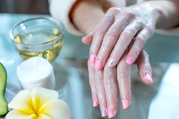 Woman applying the cream on hands nourishing them with natural cosmetics. Concept of hygiene and care for the skin