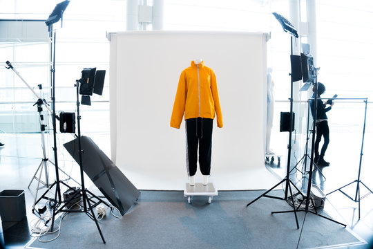Modern Photo studio booth with LED professional lighting equipment around Yellow Orange Clothes dress on Mannequin over White background, one stop service for fast work catalog shooting Camera