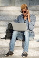 Freelance programmer talking to client on the phone and woring on laptop when sitting outdoors
