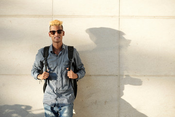 Portrait of cool young man in sunglasses standing at wall with big backpack