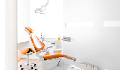 Behandlungsraum beim Zahnarzt mit orange farbenen Stühlen