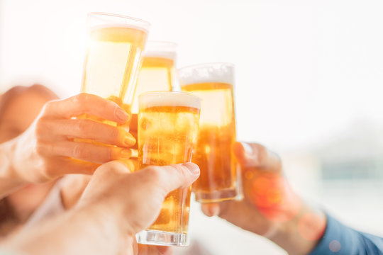 Group of happy friends drinking beer outdoors together - concept of friendship and celebration