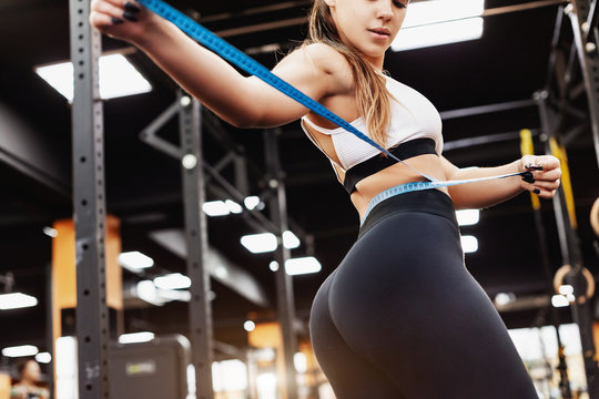 Young fitness bikini girl with a perfect figure measures her waist with a measuring tape. Concept of goal to the perfect figure with the help of fat burning workouts