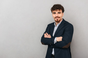 Handsome young business man isolated over grey wall background.
