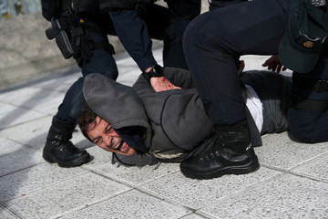 Police officers detain a striking taxi driver during a taxi strike against regulation of ride-hailing and car-sharing services such as Uber and Cabify in Madrid