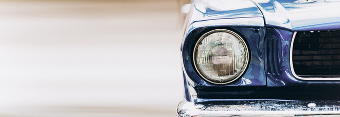 Wide closeup headlights of retro muscle car. Car exterior detail
