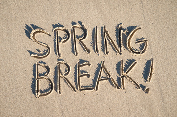 Excited Spring Break! message handwritten on the smooth sand of an empty beach with abundant sunshine
