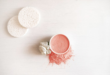 Red cosmetic clay on white wooden background.