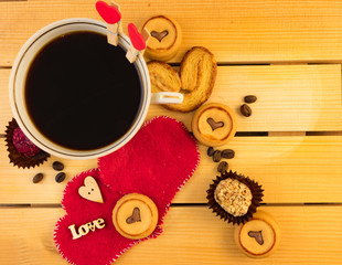Cup of coffee and cookies on wooden background.