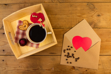Cup and envelope on wooden background.