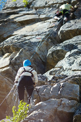 Foto op Aluminium Alpinisme A girl climber insures a partner on a rocky terrain. Two person rope.