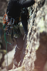 Climbing tools hanging on the climber's belt closeup. Climbing gear and equipment.