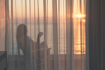 Naked beautiful female wrapped in a blanket sitting on a chair with cup of coffee behind the transparent curtains on the glass balcony early morning at sunrise. Sea view