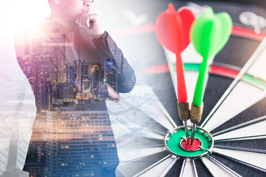 the double exposure image of the businessman standing overlay with cityscape and dart board image. the concept of business, dart board, direction and future.