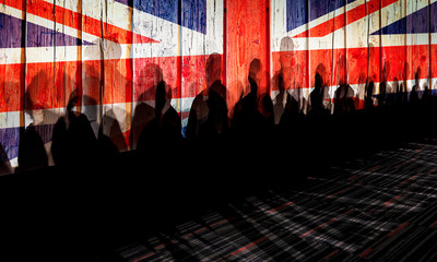 Lot of people shadows against UK flagged fence