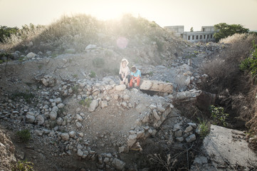 war concept of two little children victims of air strike sitting on destroyed building suffering