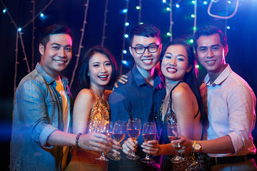 Group of happy friends drinking champagne at party in club
