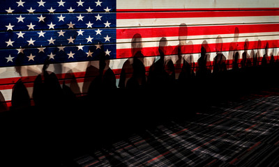Lot of people shadows against USA flagged fence