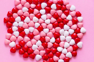 Multicolored candy or Pills in the shape of hearts. Concept Valentine's Day or Medicine, Pharmacy, Cardiology. Pink background.
