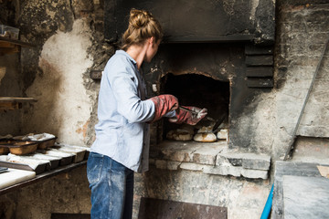 Rear view of woman baking loaves of bread in brick oven