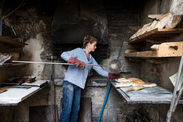 Young woman baking loaves of bread in an outdoor brick oven, Tuscany, Italy.