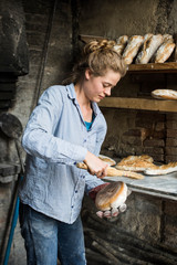 Young woman holding bread loaf outdoors