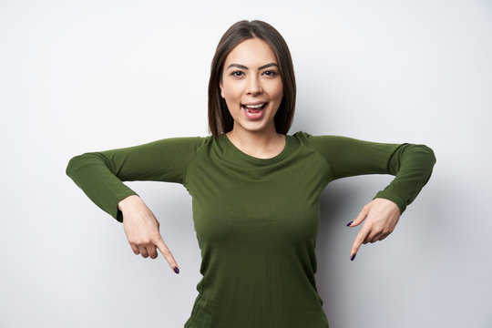 Happy woman pointing down with two fingers
