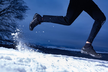 Athlete man is running during winter training outside in cold snow weather on the hills