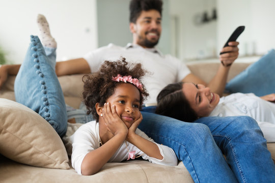Family watches movie while sitting on the couch